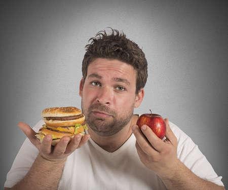 Photo pour Man undecided between diet and junk food - image libre de droit