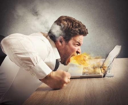 Foto de Businessman spits fire and melts the computer - Imagen libre de derechos