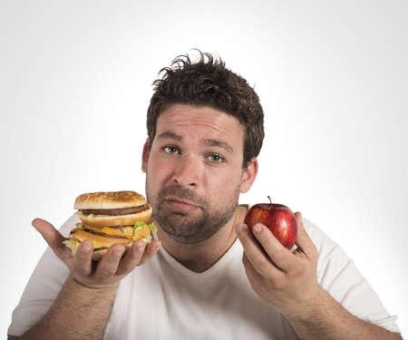 Foto de Man undecided between diet and junk food - Imagen libre de derechos