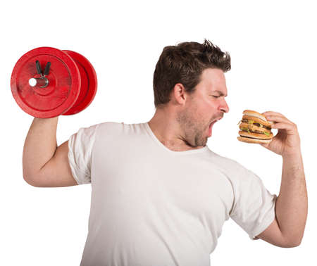 Photo for Fat man lifts weights eating a sandwich - Royalty Free Image