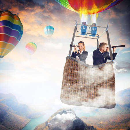 Photo for Businesspeople with binoculars in hot air balloon - Royalty Free Image
