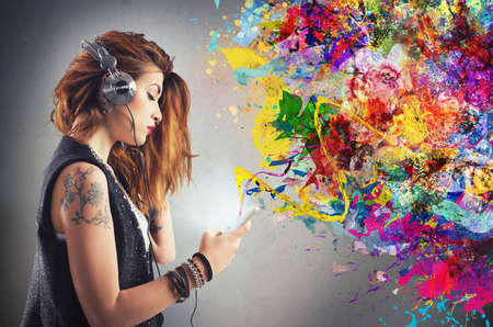 Photo for Tattoo girl listens to music with headphones - Royalty Free Image