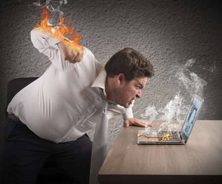 Foto de Angry man gives fiery fist to computer - Imagen libre de derechos