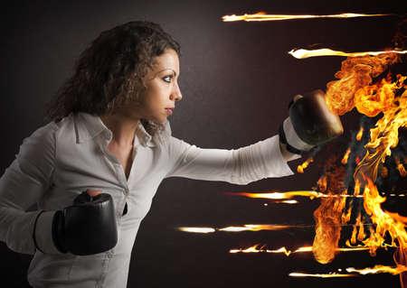 Foto de Determined woman with boxing gloves fights fire - Imagen libre de derechos