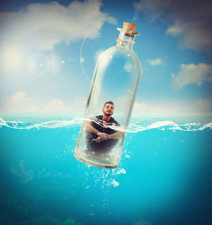 Photo pour Boy travels in bottle in the ocean - image libre de droit