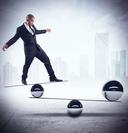 Photo pour Businessman balancing on boards with iron balls - image libre de droit