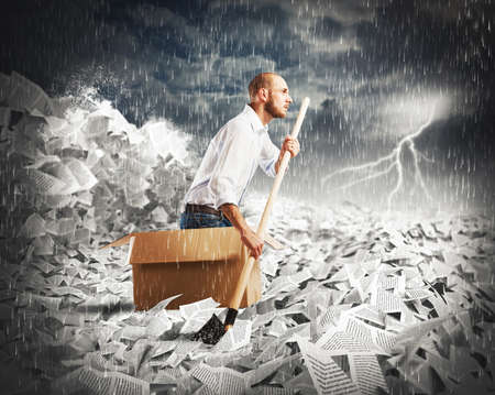 Foto de Concept of bureaucracy with man paddling in a sea of sheets - Imagen libre de derechos
