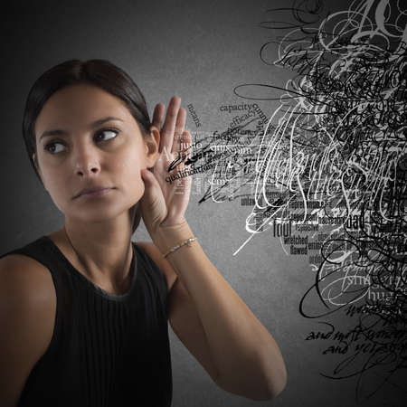 Foto de Confused Woman listen to words in disorder - Imagen libre de derechos