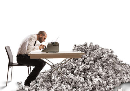 Foto de Overworked exhausted businessman writes with a typewriter - Imagen libre de derechos