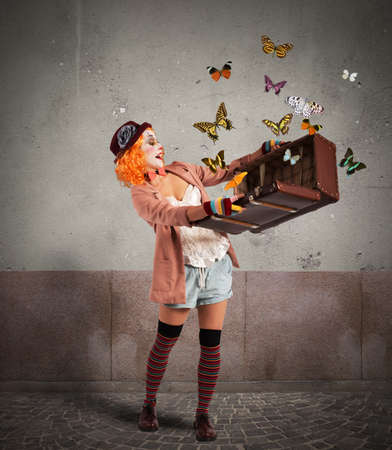 Photo for Clown opens a suitcase which emerges butterflies - Royalty Free Image