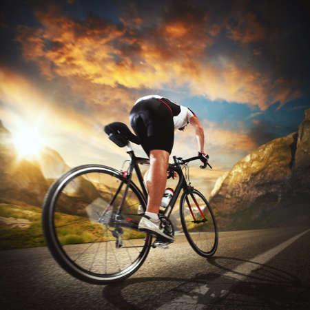 Foto de Cyclist rides on the road between mountains - Imagen libre de derechos