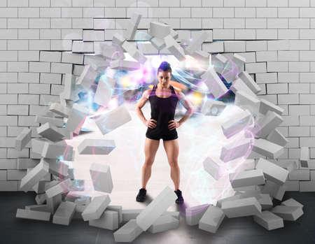 Foto de Muscular woman behind a broken brick wall - Imagen libre de derechos