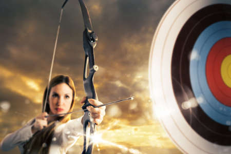 Photo for Woman with bow and arrow aiming a target - Royalty Free Image