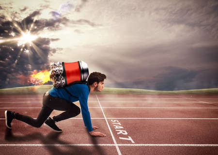 Photo pour Boy with rocket on his back on running track - image libre de droit