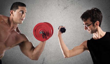 Foto de Boys are confronted by lifting a dumbbell weights - Imagen libre de derechos