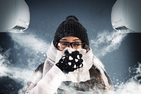 Photo pour Woman with wool scarf and gloves because of air conditioning very powerful - image libre de droit