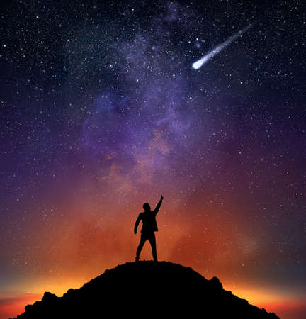 Photo for Businessman on a mountain indicate a falling star - Royalty Free Image