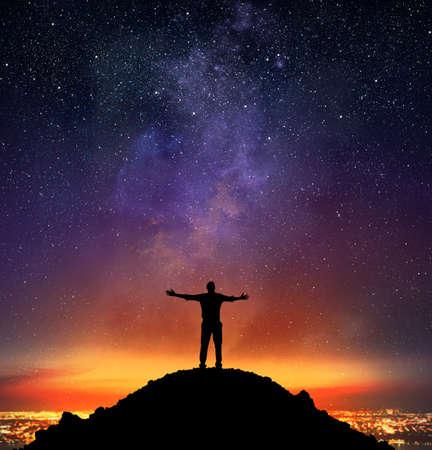 Foto de Businessman exults on a mountain with starry sky background - Imagen libre de derechos