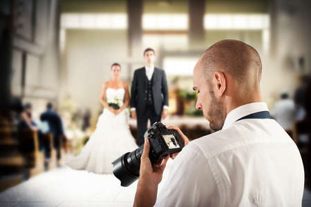 Foto de Photographer looks at the screen of camera to a wedding - Imagen libre de derechos
