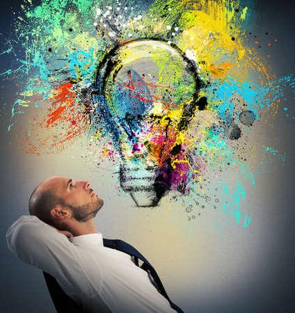 Foto de Businessman sitting in a chair watching a light bulb drawn and thinks a new creative idea - Imagen libre de derechos