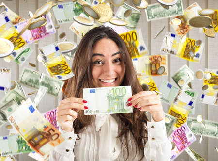 Foto de Happy businesswoman shows a 100 euro banknote with rain of money background - Imagen libre de derechos