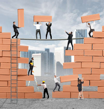 Photo pour Business person built together a big brick wall - image libre de droit