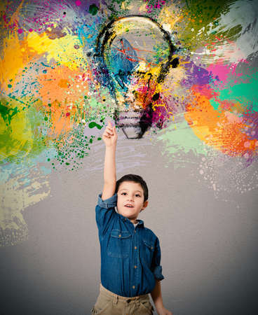 Foto de Child indicates a big colored bulb designed - Imagen libre de derechos
