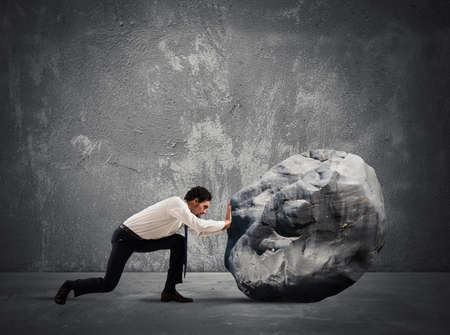Photo for Businessman pushing a heavy boulder with great effort - Royalty Free Image