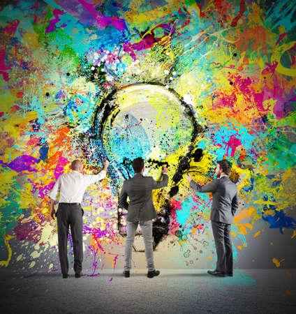 Photo pour Business person paint together a big colored lightbulb on the wall - image libre de droit