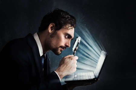 Foto de Businessman look with magnifying glass at the computer screen - Imagen libre de derechos