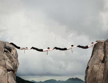 Photo pour Businessmen working together to form a bridge between two mountains - image libre de droit