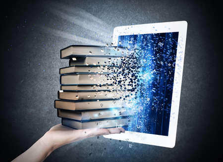 Photo pour Reading books with an E-book - image libre de droit