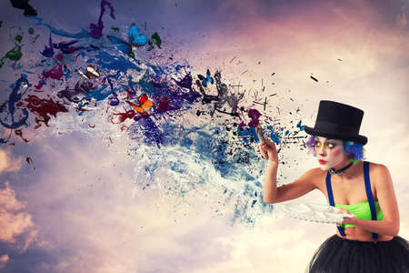 Photo pour Painter clown paints the sky with colorful splash effect - image libre de droit