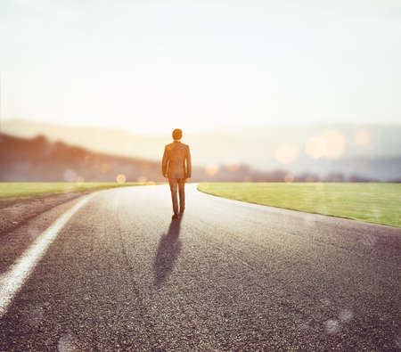 Photo pour Man walks on an unknown road for a new adventure - image libre de droit
