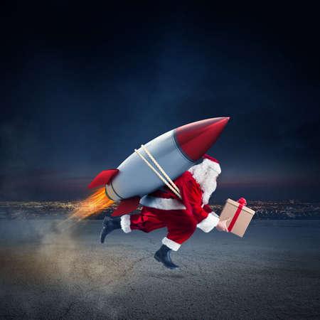Foto de Santa Claus with gift box ready to fly with a rocket in the sky - Imagen libre de derechos