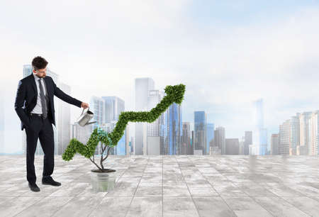Foto de Businessman that watering a plant with a shape of arrow. Concept of growing of company economy . - Imagen libre de derechos