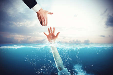 Photo pour Business man tends his hand to save a person drowning - image libre de droit