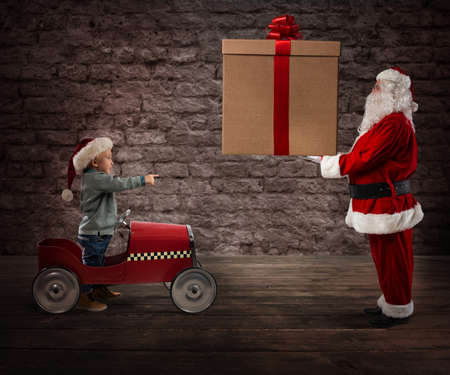 Photo for Santa Claus deliver a CHristmas gift to a child - Royalty Free Image
