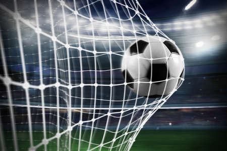 Photo pour Soccer ball scores a goal on the net - image libre de droit