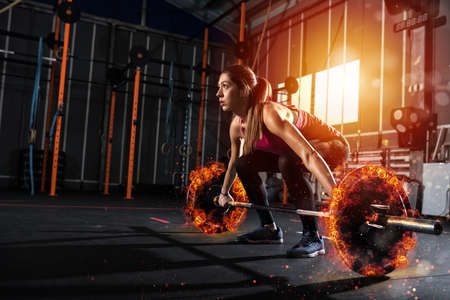 Foto de Athletic girl works out at the gym with a fiery barbell - Imagen libre de derechos