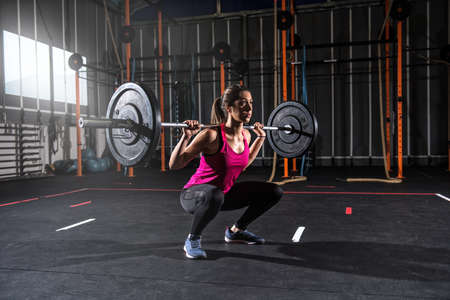 Foto de Athletic girl works out at the gym with a barbell - Imagen libre de derechos
