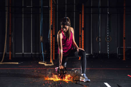 Foto de Athletic girl works out at the gym with a fiery kettlebell - Imagen libre de derechos
