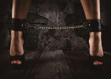Foto de Sensual provocation of a sexy bdsm woman with chained legs - Imagen libre de derechos
