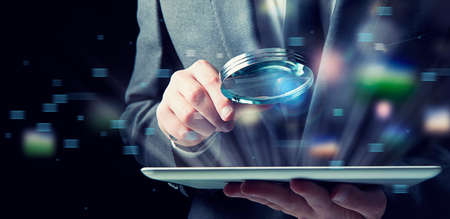 Photo pour Businessman examines a tablet with a magnifying glass. Concept of internet security - image libre de droit