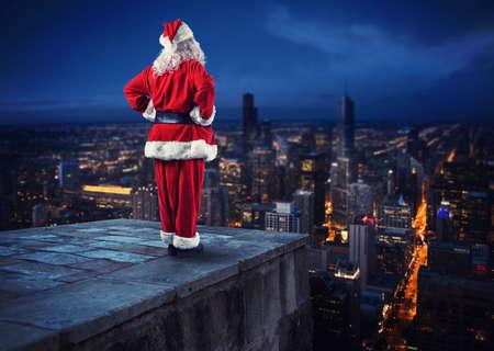 Photo pour Santa Claus looks down on the city waiting to deliver the presents - image libre de droit