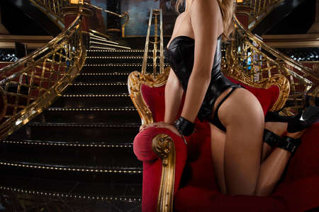 Foto de Sensual provocation of a sexy bdsm woman on an armchair - Imagen libre de derechos