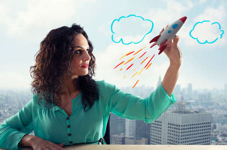 Photo pour Businesswoman launches his company with a rocket. Concept of startup and innovation. - image libre de droit