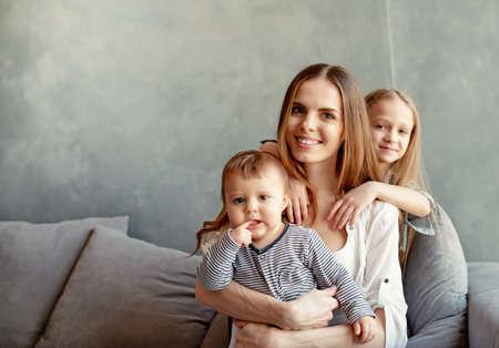 Foto de Happy young mother with her children at home - Imagen libre de derechos