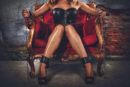 Foto de Sensual provocation of a sexy bdsm woman on an armchair - Imagen libre de derechos