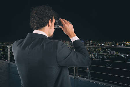 Photo for Businessman looks at the city with binoculars during night. Future and new business opportunity concept - Royalty Free Image